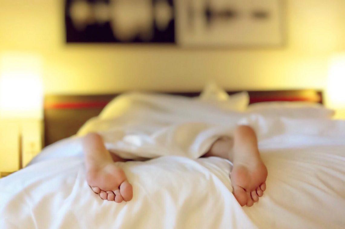 En person ligger i sengen og kan ikke sove